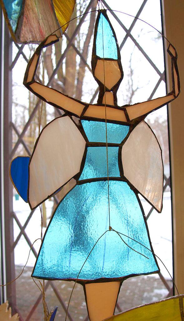 Witraż w postaci tańczącej wróżki z anielskimi skrzydłami na tle rozmytego okna z czarnymi kratami.