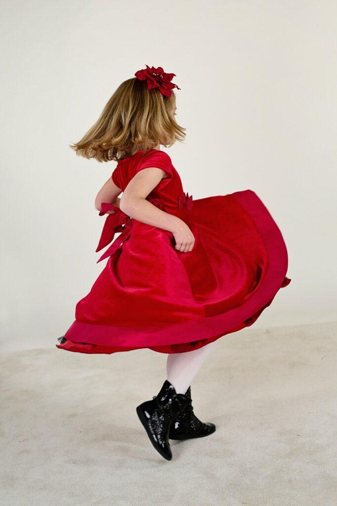 Roztańczona mała dziewczynka z upiętym na długich włosach kwiatem, uchwycona bokiem w tanecznym obrotowym ruchu. Twarz niewidoczna.