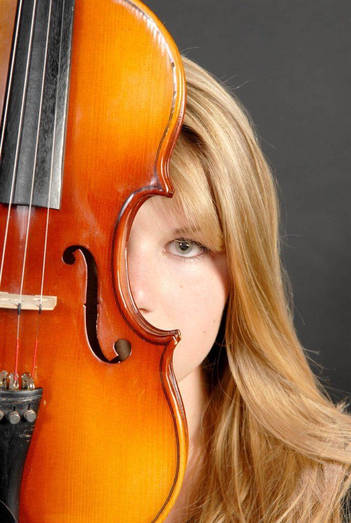 Twarz młodej dziewczyny z długimi włosami w połowie schowanej za pudłem rezonansowym skrzypiec.