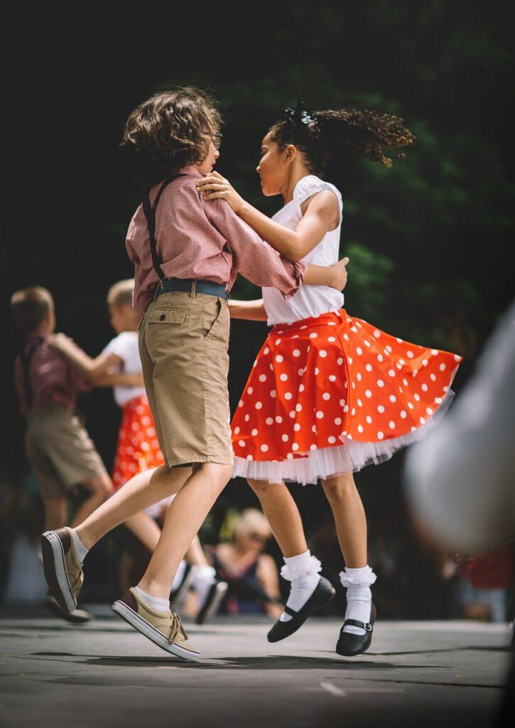 Para tańczących dzieci uchwycona w podskoku tanecznym na tle innej pary dzieci. Chłopiec ubrany w krótkie spodenki na szelki koszulkę. Dziewczynka w rozkloszowaną spódniczkę na koronkowej halce, skarpetki z kryzką i białą przylegającą bluzeczkę.