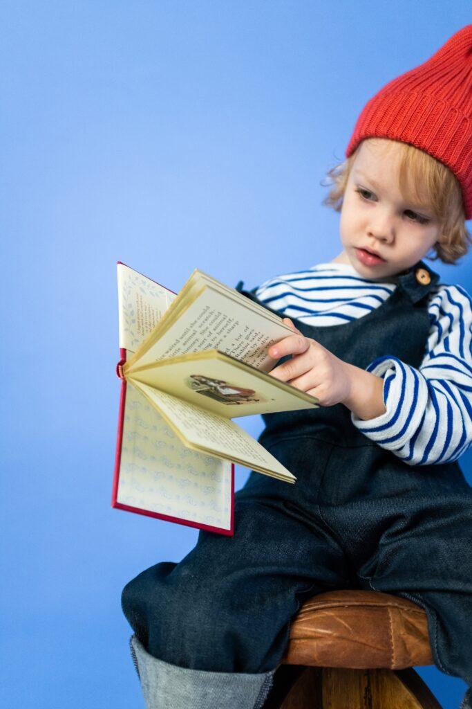 Około siedmioletnie dziecko siedzące na wysokim okrągłym taborecie z zainteresowaniem czytające otwartą książeczkę.
