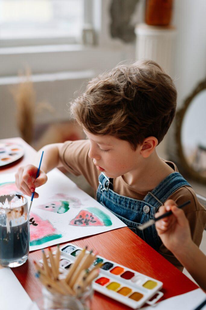 Około 8 letni chłopiec siedzi w pracowni malarskiej i na białej kartce maluje farbami cząstki arbuza.