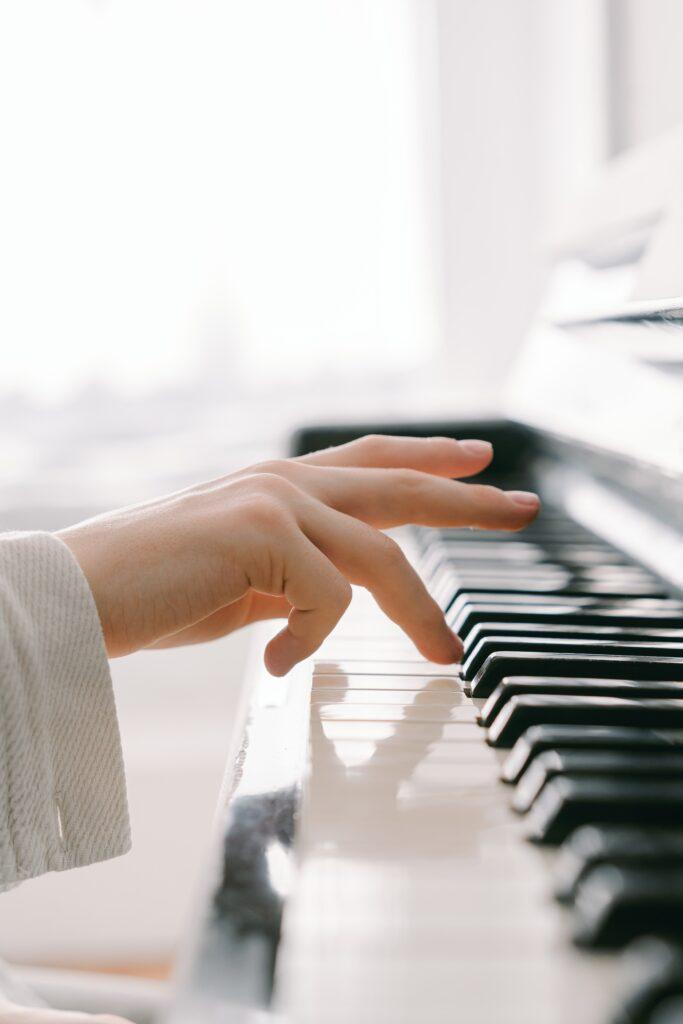 Ręka młodego pianisty uderzająca czwartym palcem w klawiaturę pianina.
