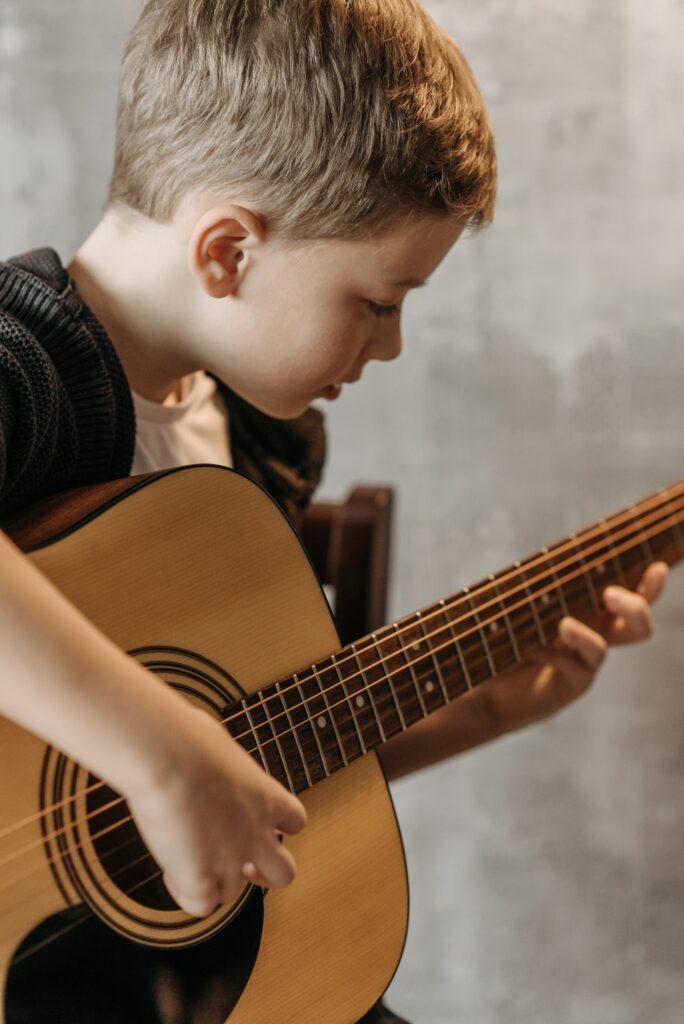 Około ośmioletni chłopiec grający na  gitarze.