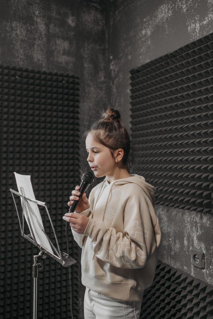 Około dziewięcioletnia dziewczynka trzymająca mikrofon stojąca przed pulpitem z białą kartką w wyciszonym dźwiękochłonnymi matami studiu nagraniowym.