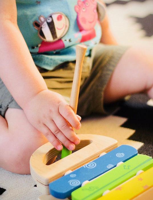 Postać małego dziecka (twarz nie widoczna) siedzącego w rozkroku, trzymającego w rączce drewnianą pałeczkę między uchwytem a kolorowymi szczebelkami drewnianych cymbałek.