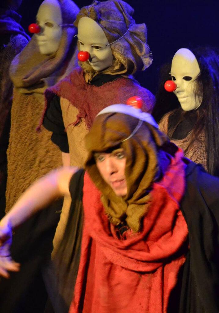 Na pierwszym planie postać przebranego w luźno zarzucone materiały młodzieńca w nakryciu głowy. W tle trzy postacie w białych, gładkich maskach z kulkowymi, czerwonymi noskami klaunów.