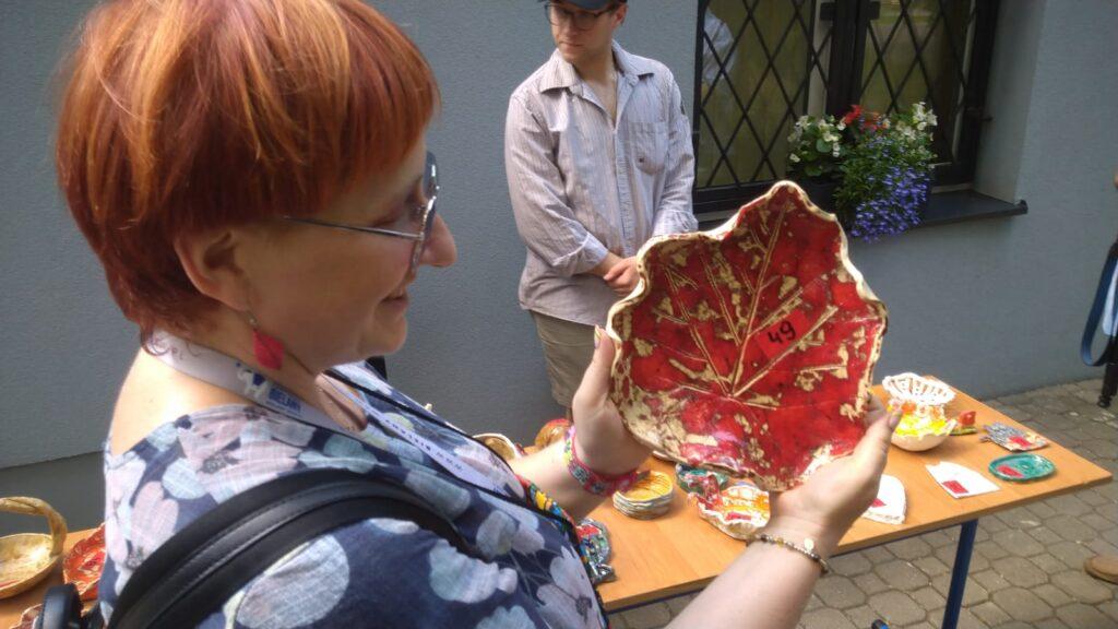 Zdjęcie z Fiesty Rodzinnej w MDK Bielany. Na fotografii kobieta pokazuje ceramiczną misę w kształcie liścia w kolorze czerwonym, w tle budynek MDKu.