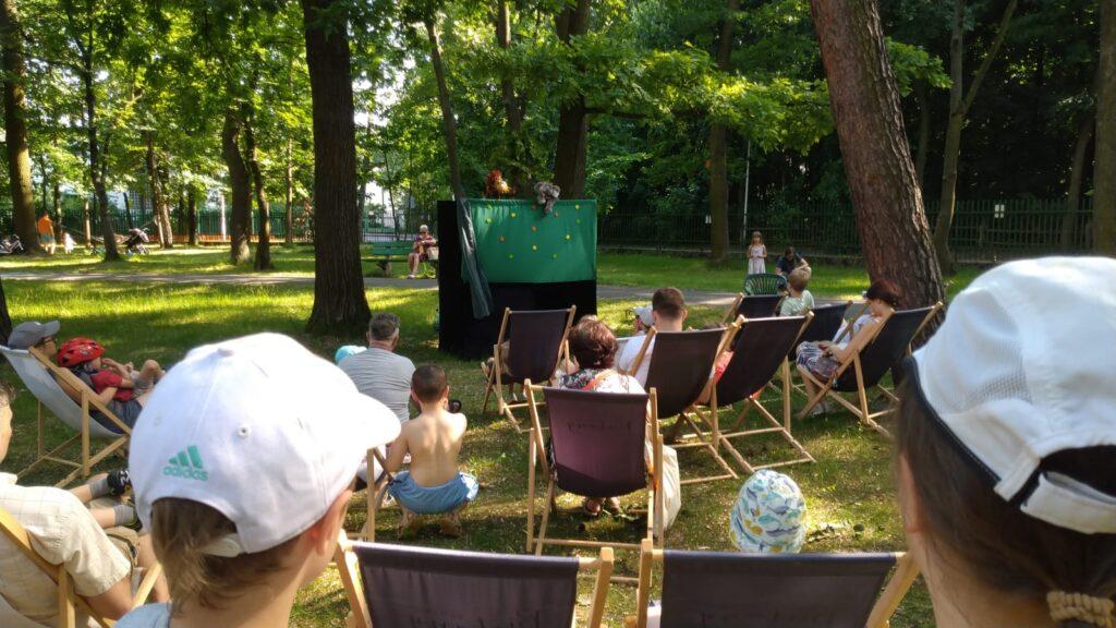 Zdjęcie z Fiesty Rodzinnej w MDK Bielany. Na fotografii ludzie leżący na leżakach i oglądający przedstawienie lalkowe w parku MDK Bielany.