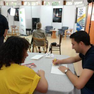 Zdjęcie z 8. Festiwalu Dużego Formatu, który odbył się 22.08.2021 w MDK Bielany. Na fotografii mężczyzna podpisuje książkę przy stole